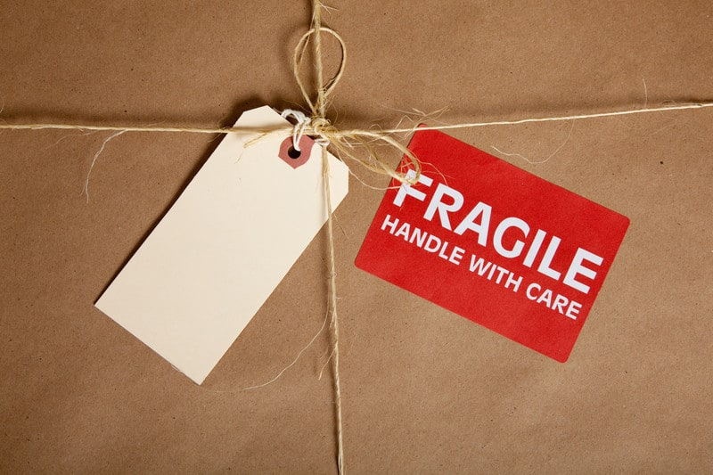 brown shipping box with a blank tag and a fragile sticker