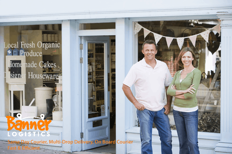 couple standing in front of UK food store business shop front smiling