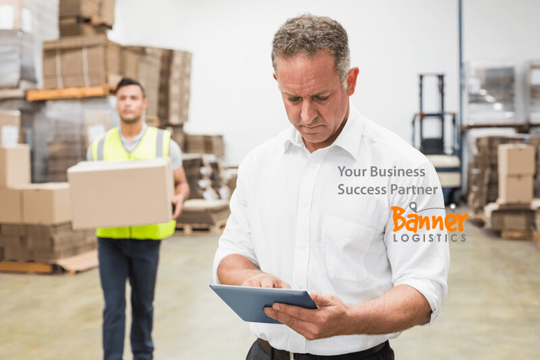 warehouse worker carrying parcel box and UK businessman holding a tablet device